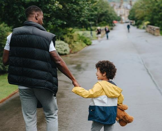 father and son walking through a park in a large city