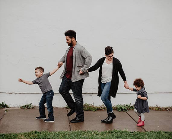 family holding hands and playing on the sidewalk