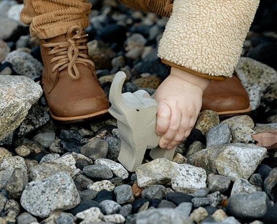 a toddlers shoes standing on rocks while playing with a toy elephant